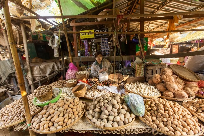 BAGAN, MYANMAR: FEBRUARY 21, 2015 : Local women sell their produce at an outdoor market in Bagan on February 21, 2015. The markets operate daily and are a gathering spot for sales and gossip, stock photo