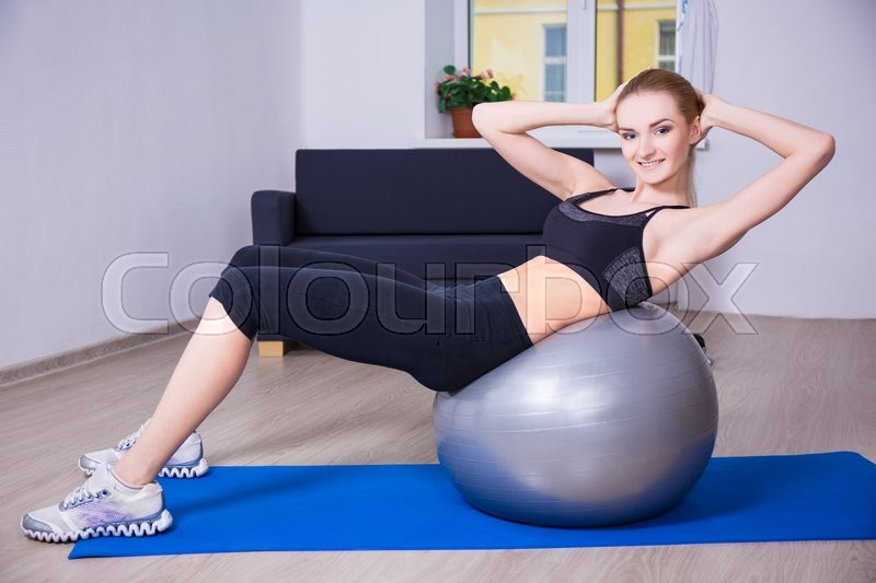 Young beautiful happy woman doing fitness exercises with pilates ball at home, stock photo