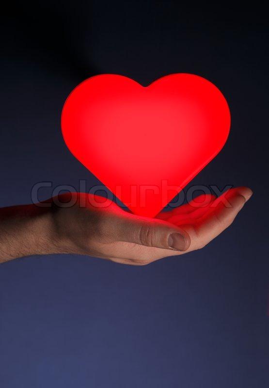 man h lt ein rot gl henden herz form in der hand stock foto colourbox. Black Bedroom Furniture Sets. Home Design Ideas