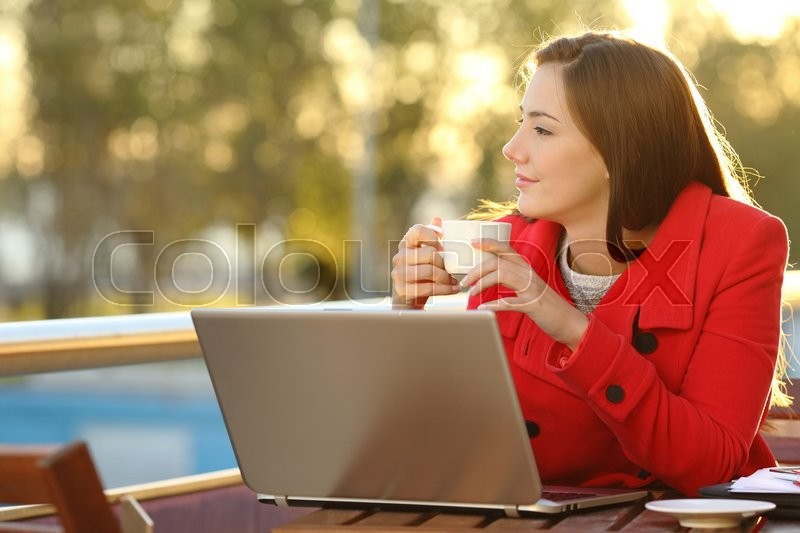 Entrepreneur with a laptop relaxing in a coffee shop and looking forward, stock photo