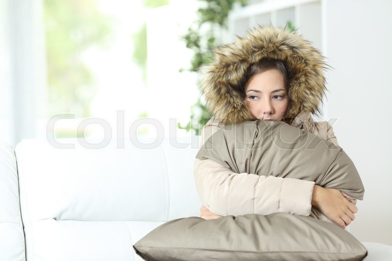 Angry woman warmly clothed in a cold home sitting on a couch, stock photo