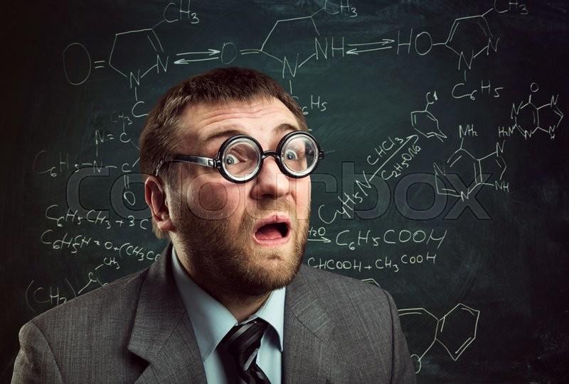 Bizarre professor in glasses thinking over chemical formulas on blackboard, stock photo