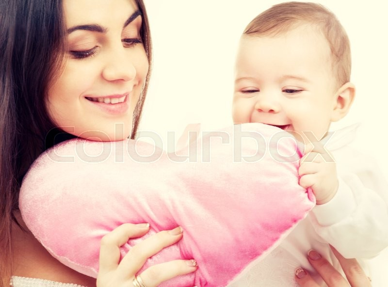 Happy baby and mama with heart-shaped pillow, stock photo