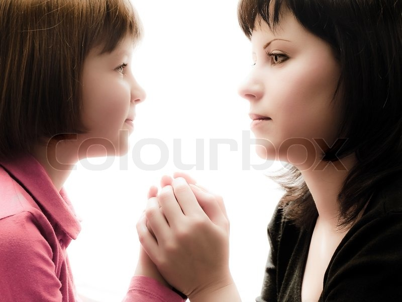 Mother and daughter sitting opposite each other, watch each other\'s eyes and hold hands, stock photo