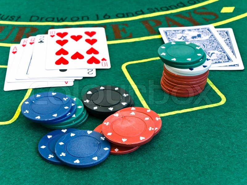 Card deck and a few color chips on the playing table in the casino, stock photo