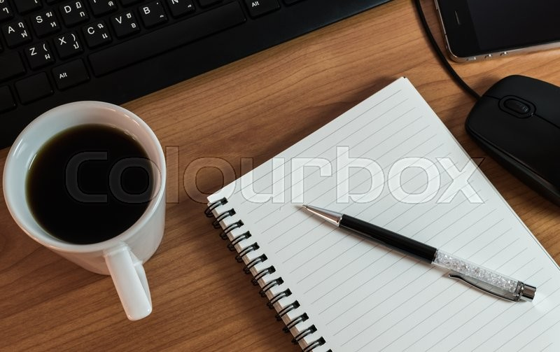 Pen on notebook with coffee computer keyboard, mouse and cell phone on wooden table, stock photo