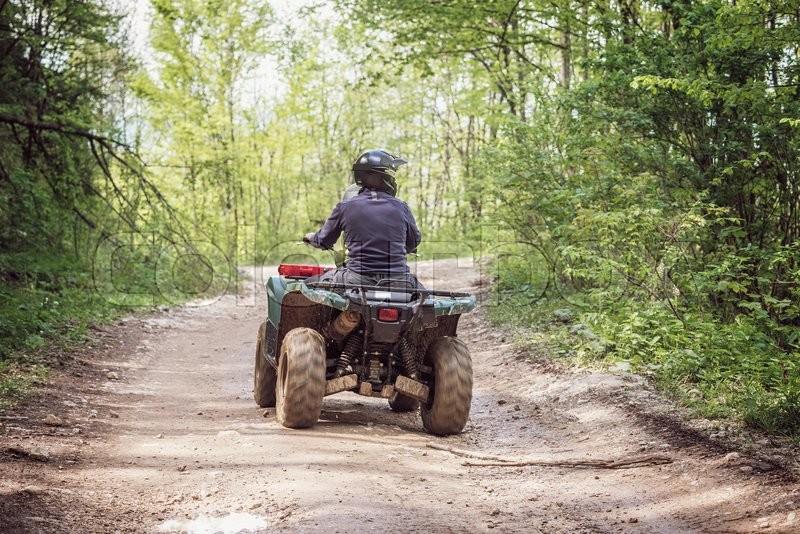 Man on the ATV Quad Bike on the mountains road. , stock photo