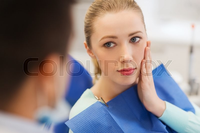 People, medicine, stomatology and health care concept - woman patient talking to male dentist and complain of toothache at dental clinic office, stock photo