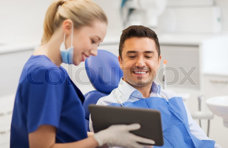 People, medicine, stomatology and health care concept - happy female dentist showing tablet pc computer to male patient at dental clinic office, stock photo