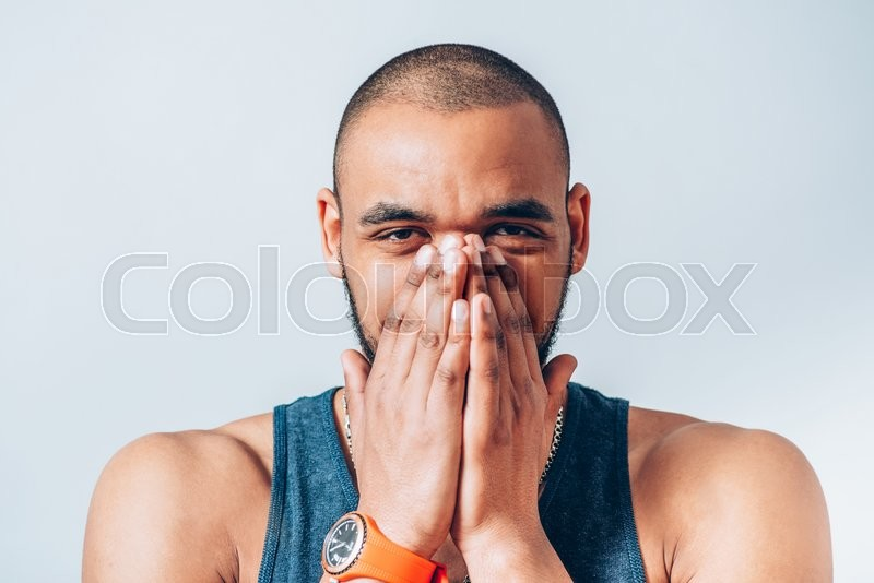 Black man laughs and covers her mouth, stock photo