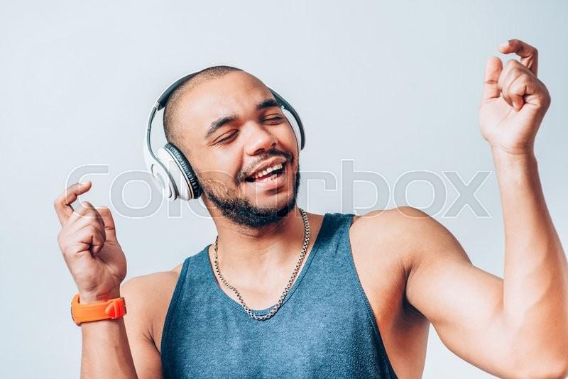 Black man listening to music on headphones | Stock Photo ...