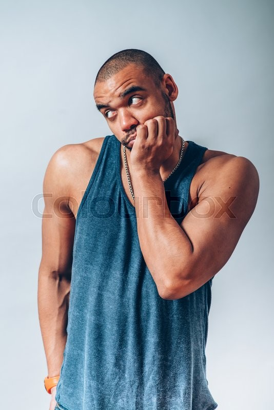 Black man backs his chin with his fist, stock photo