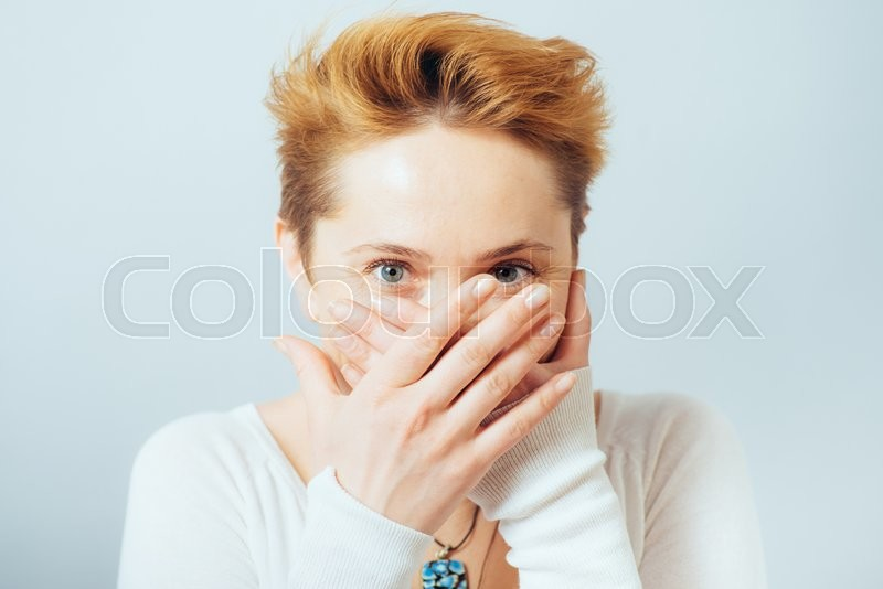 Woman covers her mouth with her hands, short hair, stock photo