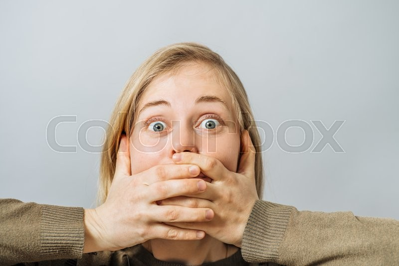 Girl covers her mouth with her hands, stock photo