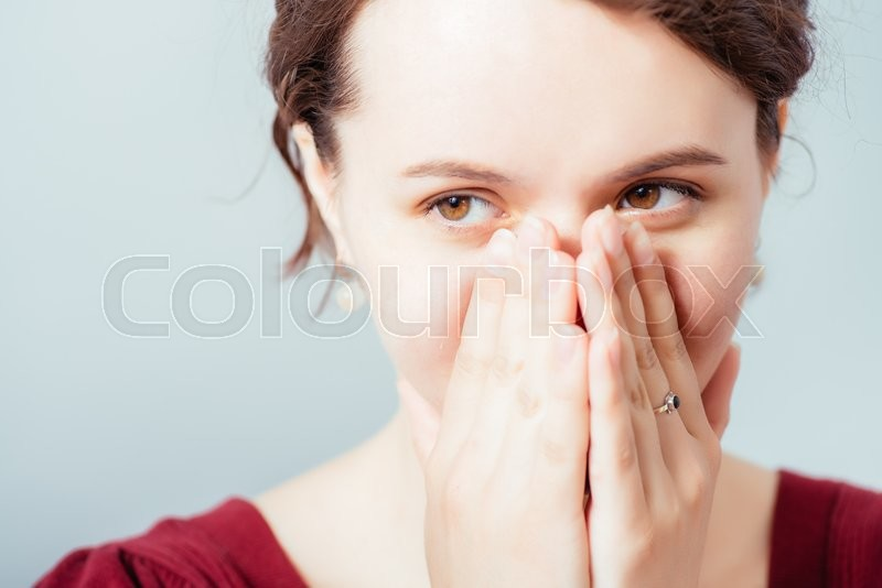 The woman smiles, covers a mouth with a palm, stock photo