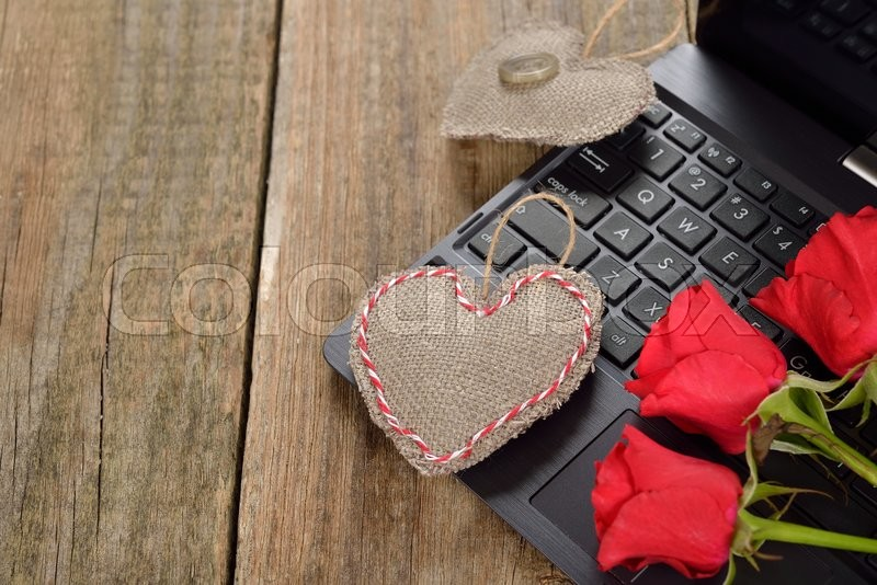Computer and roses on a wooden background, Valentine\'s Day concept, stock photo