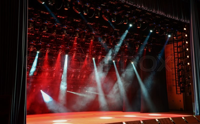 Illuminated empty concert stage with smoke and light beams ...