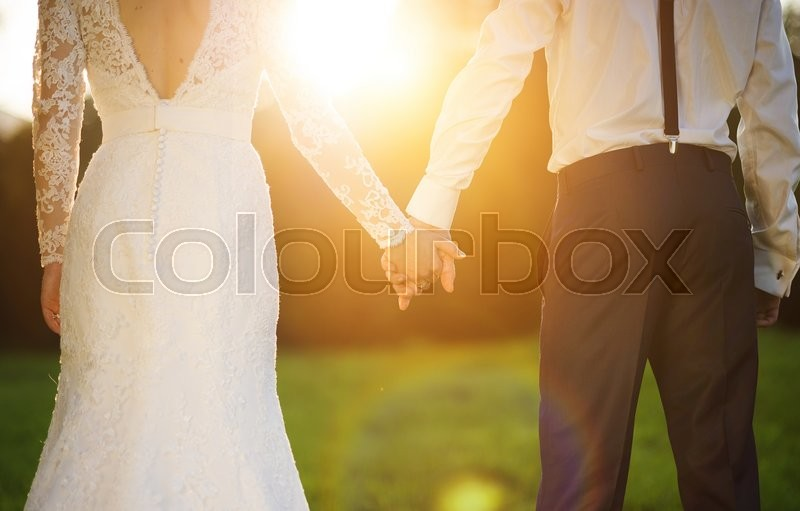Young wedding couple holding hands as they enjoy romantic moments outside on a summer meadow, stock photo