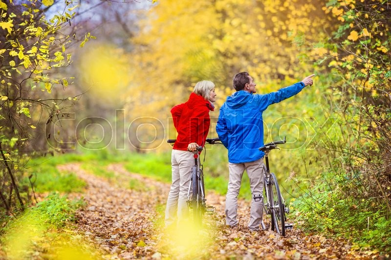 Active seniors having walk with bike in autumn nature. They having romantic time outdoor, stock photo