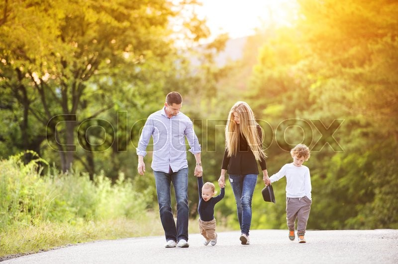Happy young family walking down the road outside in green nature, stock photo