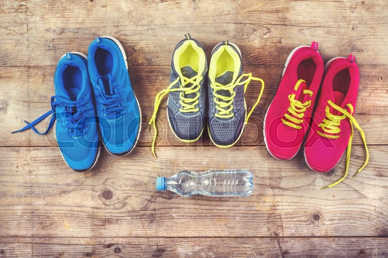 Various pairs of colorful sneakers laid on the wooden floor background, stock photo