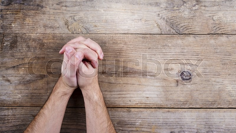 Hands of praying young man on a wooden desk background, stock photo