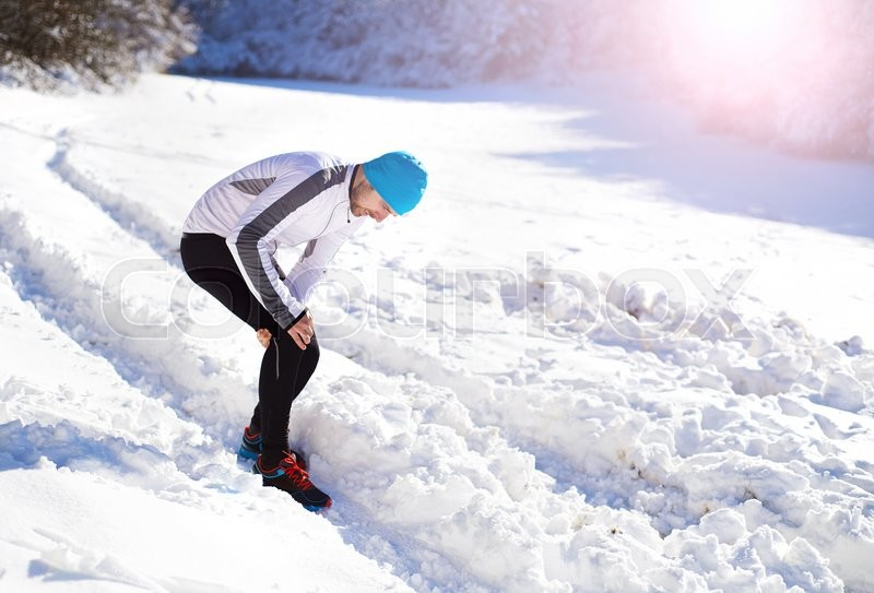 Injury of a young sportsman jogging outside in sunny winter park, stock photo
