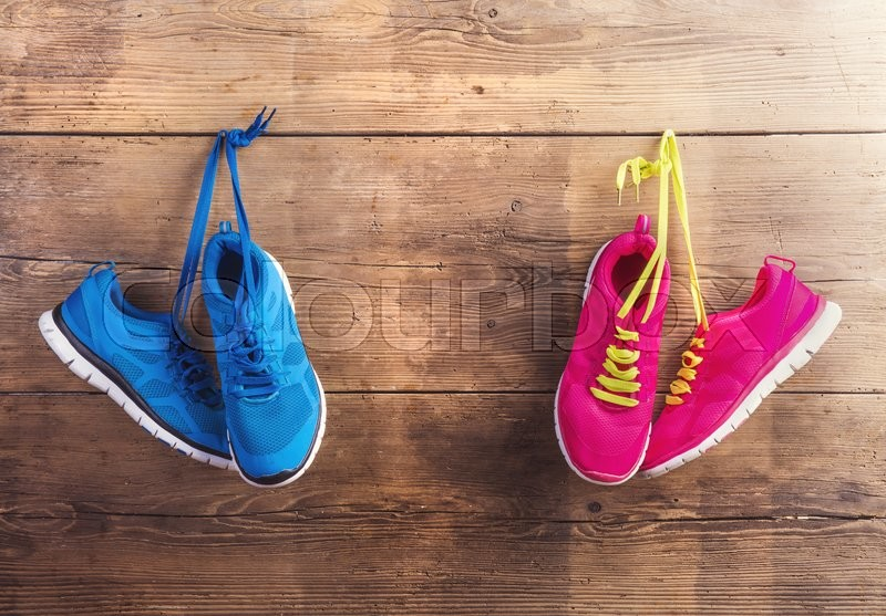 Two pairs of sneakers hang on a nail on a wooden fence background, stock photo