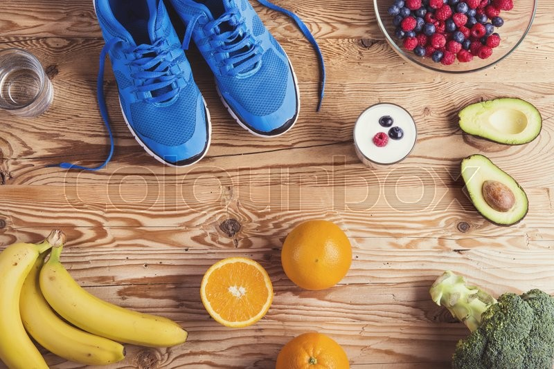 Pair of running shoes and healthy food composition on a wooden table background, stock photo