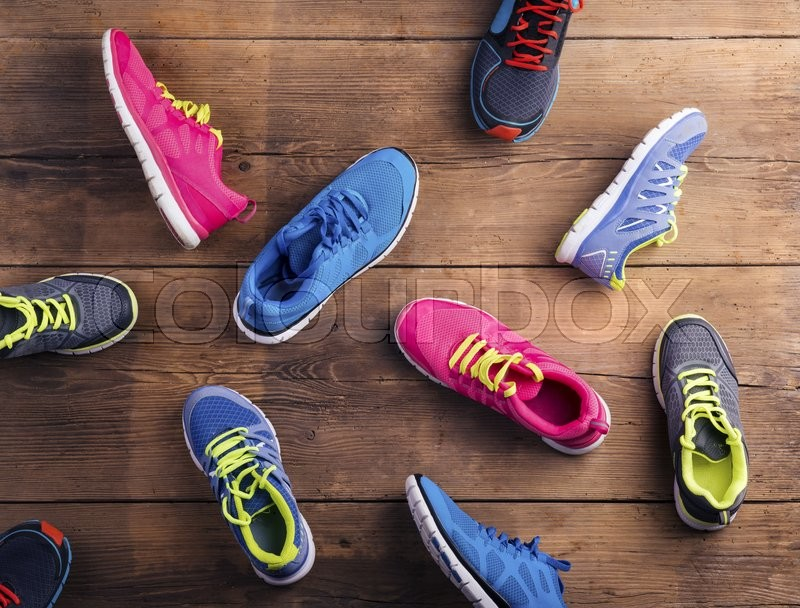 Various running shoes laid on a wooden floor background, stock photo