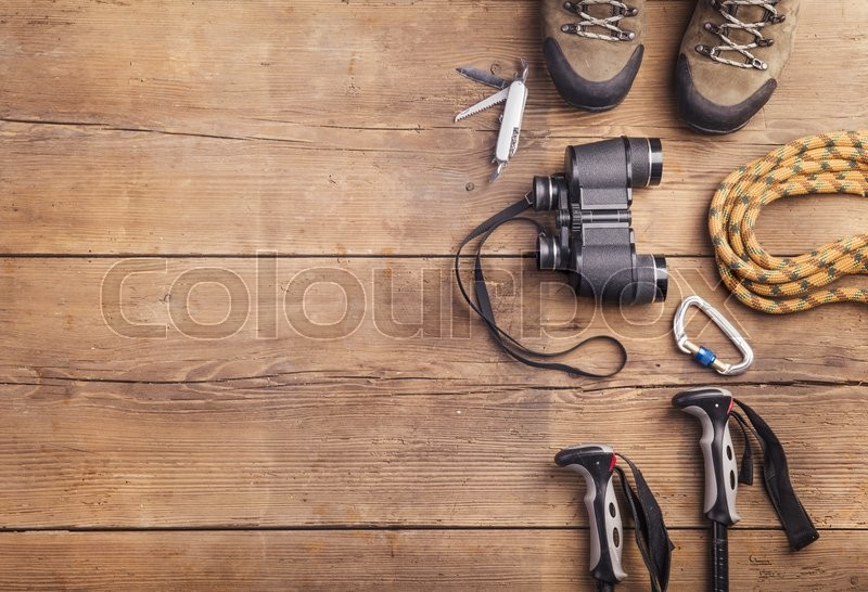 Equipment for hiking on a wooden floor background, stock photo