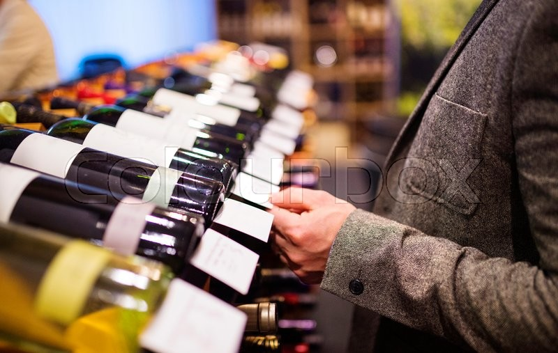 Unrecognizable young man in a wine shop choosing a wine, stock photo