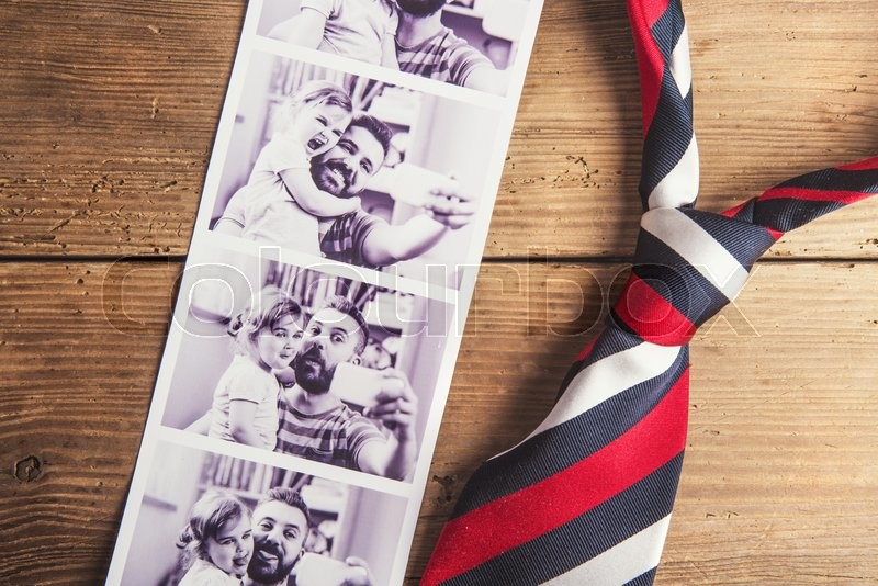 Pictures of father and daughter and colorful tie laid on wooden floor background, stock photo