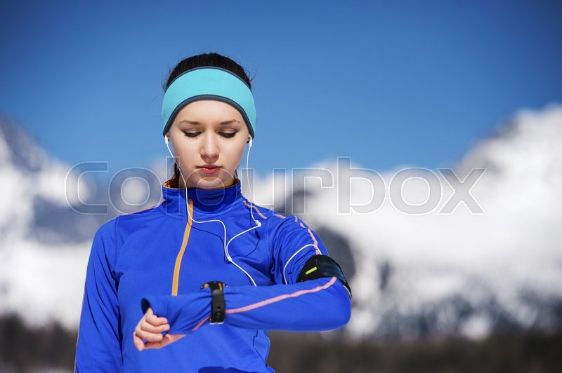 Young sportswoman jogging outside in sunny winter mountains, stock photo