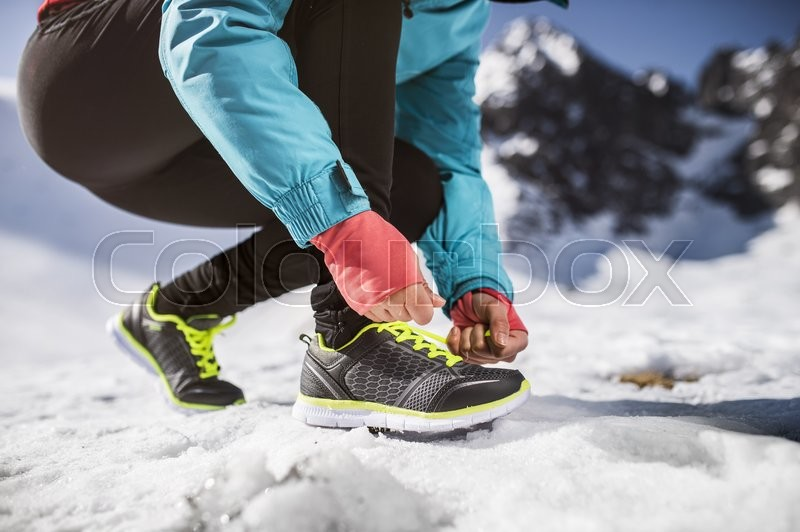 Unrecognizable woman jogging outside in sunny winter mountains, stock photo