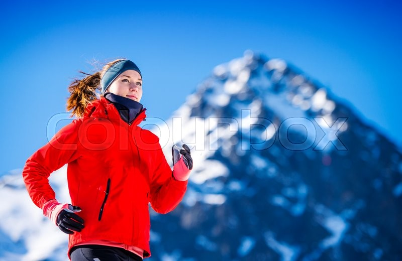 Young woman jogging outside in sunny winter mountains, stock photo