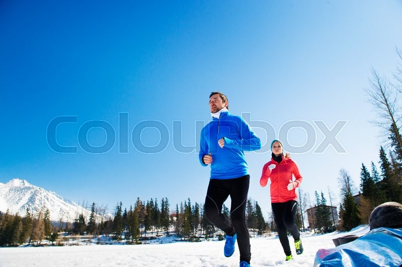 Young couple jogging outside in sunny winter mountains, stock photo