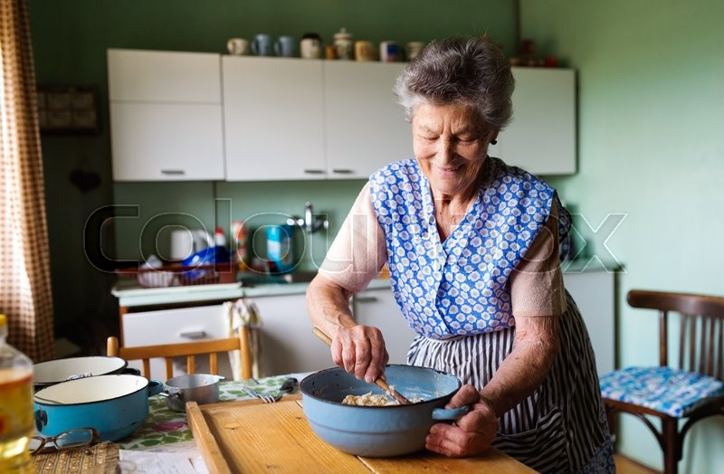 Senior woman baking pies in her home kitchen. Mixing ingredients, stock photo