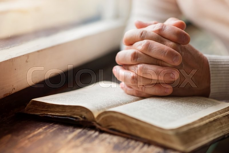 Unrecognizable woman holding a bible in her hands and praying, stock photo