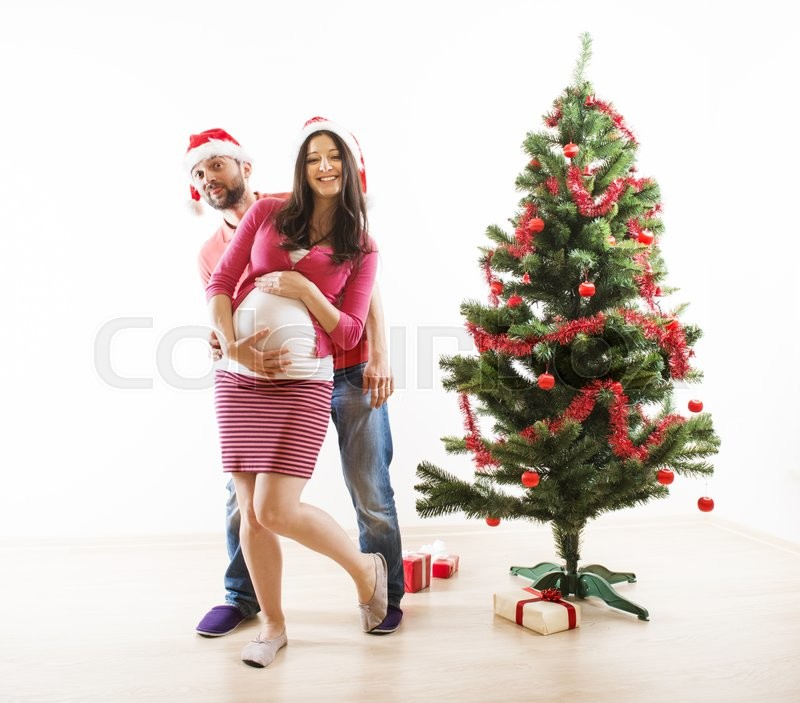 Young couple is dancing close to christmas tree. Woman is pregnant, stock photo