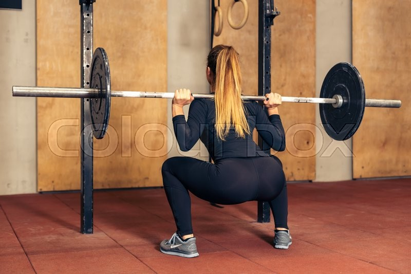 Back view young adult girl doing heavy duty squat in gym with barbell.Sexy woman with perfect abs doing squat exercises. Fitness blonde fit woman in great shape, stock photo