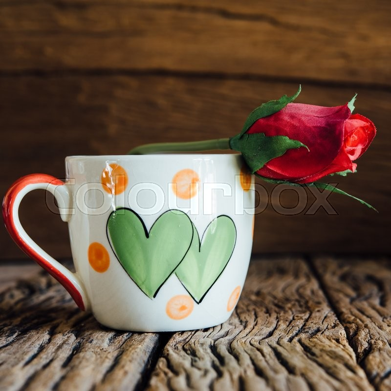 Vintage love cup with rose on old wood background, stock photo