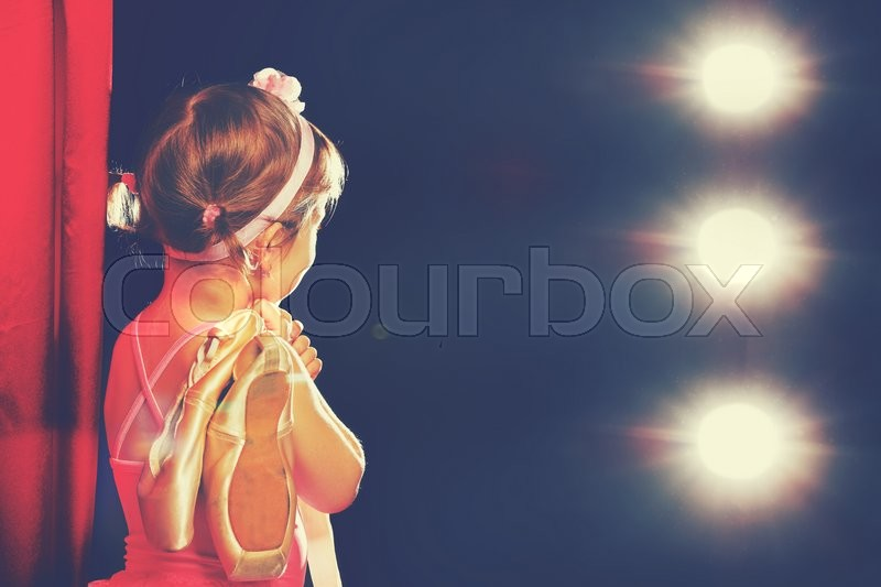 Little child girl ballerina ballet dancer on the stage in red side scenes and looking in odeum, stock photo