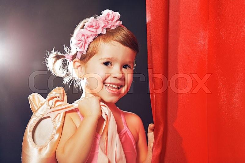 Little child girl ballerina ballet dancer on the stage in red side scenes, stock photo