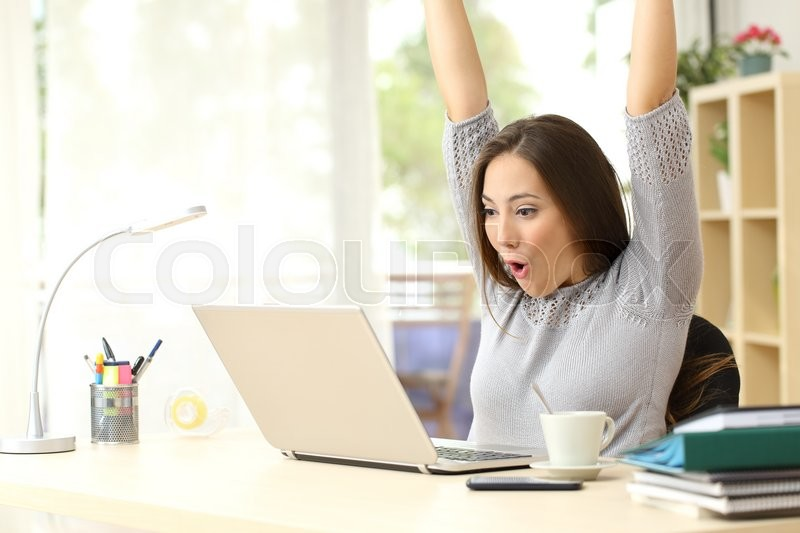 Euphoric and surprised winner winning online watching a laptop at home, stock photo