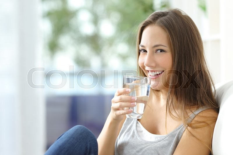 Girl drinking water sitting on a couch at home and looking at camera, stock photo