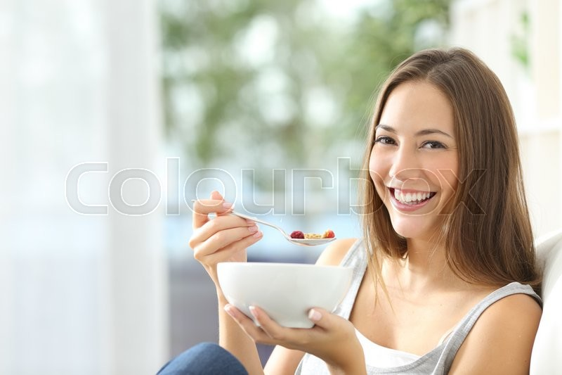 Casual happy woman dieting and eating cornflakes sitting on a couch at home, stock photo