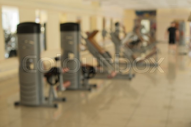 Training apparatus in gym. Blurred picture of gym. Fitness stations and trainers in hall. People are training in gym on the background, stock photo