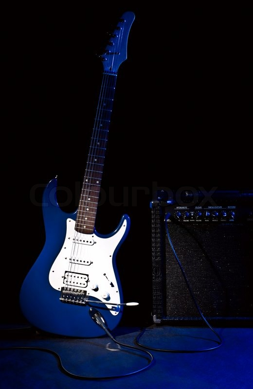 Electric Guitar And Combo Amplifier In Rays Of Blue Light On Black Background