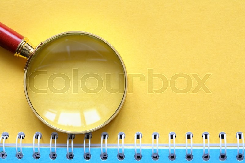 Investigation Symbol Magnifying Glass On Open Spiral Notebook With